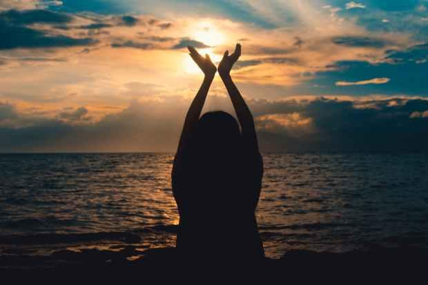 person raising hands near sea at sunset